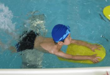 ビート板を持って泳いでいる少年