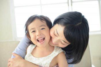 女の子と後ろから抱きつくお母さん