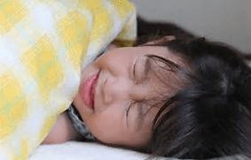 布団で寝ながら苦しい表情を浮かべている女の子