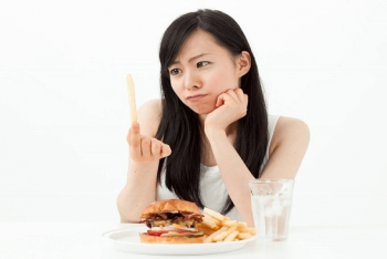 ハンバーガーとポテトを目の前に食べることに迷いのある女性